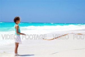 Adorable little girl playing with gymnastic ribbon on the beach. SLOW MOTION