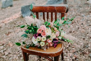 Beautiful wedding bouquet on an old brown chair standing outside.