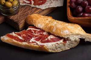 Jamon Iberico with white bread, olives on toothpicks and fruit on a dark background