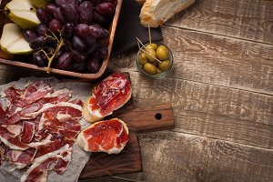 Jamon Iberico with white bread, olives on toothpicks and fruit on a wooden background. Top view with copy space