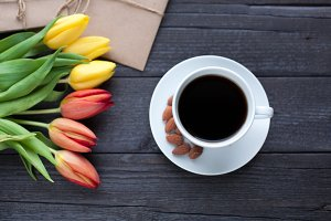 white cup of coffee with yellow and orange tulip on black wood background