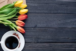 white cup of coffee with yellow and orange tulip on black wood background. copy space