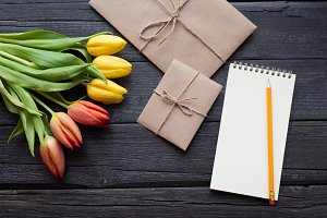 Empty notebook, pencil and yellow and red tulips flowers on vintage wooden background. Selective focus. Place for text. Flat lay