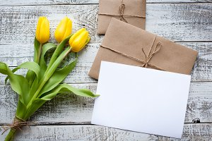 Fresh yellow tulips and empty tag on teal painted wooden background. Selective focus. Place for text. Square image