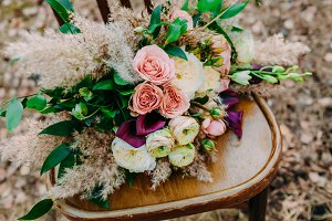 Beautiful wedding bouquet on an old brown chair standing outside in park.