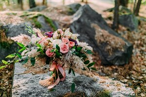Beautiful wedding bouquet lying on a stone in the park. Autumn wedding