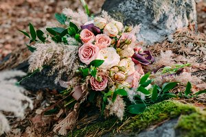Beautiful wedding bouquet consisting of different flowers lying on a stone in the park. Autumn wedding