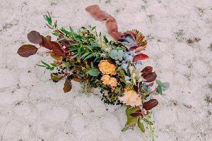 Gorgeous wedding bouquet consisting of different flowers lying on a ground in the park. Bunch of flowers