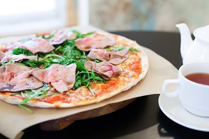 Pizza with roast beef and rocket salad on a table