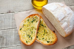 Fried bread with olive oil, garlic and herbs on a wooden table. Rustic style