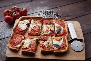 rustic italian pizza with mozzarella, cheese and basil leaves