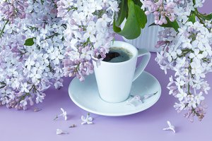 Lilacs in white jug with coffee