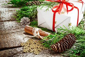 Christmas box and conifer branches and cones closeup. Selective