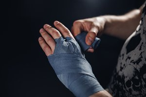Man is wrapping hands with blue boxing wraps
