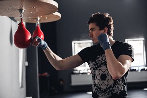 Handsome man training punch for punching pear