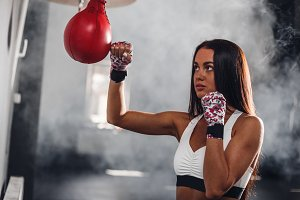 Attractive female boxer at training with boxing pear