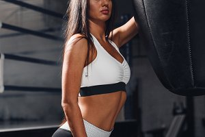 Concentrated woman doing a fitness boxing workout with a punching bag