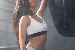 Beautiful girl in sports uniform posing near a punching bag in the gym