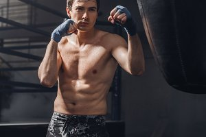 Young sportsman at boxing workout with a punching bag