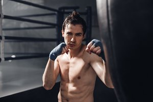Portarait of young boxer man in boxing wraps with punching bag