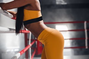Closeup of a young womans body against the backdrop of a boxing ring