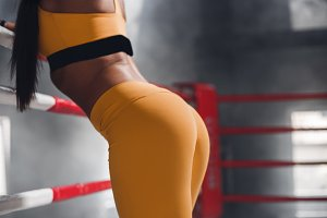 Sexy beautiful athletic ass, female in boxing ring leaning on rope