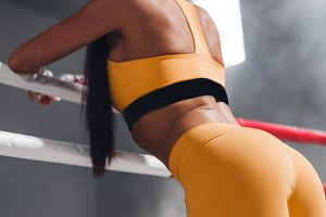 Rear view of the figure of a young athletic woman standing on ring and resting