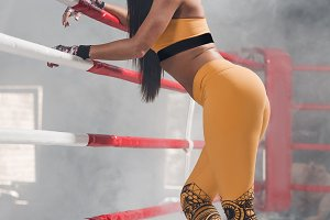 Young fitness beautiful brunette girl ring leaning on rope in boxing ring
