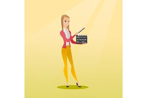 Smiling woman holding an open clapperboard.