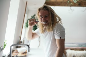 Man smiling while brushing his teeth