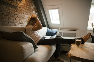Young man with laptop in loft interior