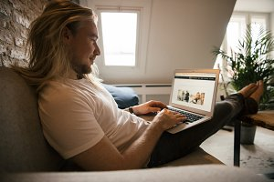 Man with long hair looking at laptop
