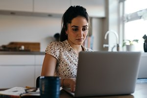 Woman at laptop in kitchen