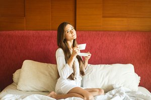 in white robe drinking tea