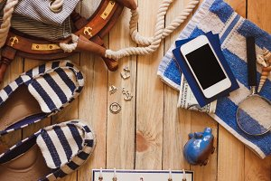 Striped espadrilles, towel, piggy bank, phone and marine decorations