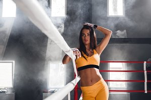 Woman after gym workout stands in the boxing ring
