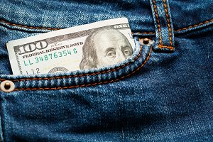 Hundred-dollar bill in jeans pocket. Close-up.