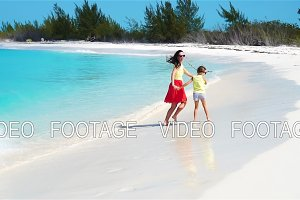 Little adorable girl and young mother at tropical beach. Family of two have a lot of fun during summer vacation. SLOW MOTION