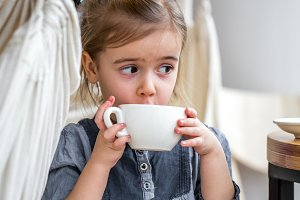 little girl drinking tea in a cafe