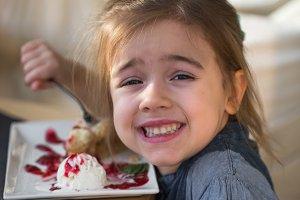 the little girl in cafe eats a dessert