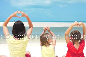 Adorable little girls and young mother on white beach. SLOW MOTION