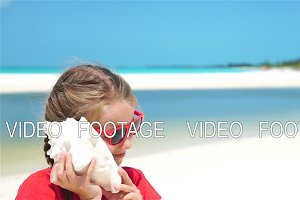 Portrait of little adorable girl listening a big seashell on the beach. SLOW MOTION