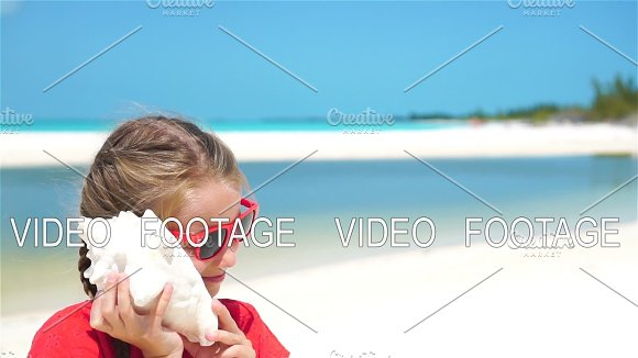 Portrait Of Little Adorable Girl Listening A Big Seashell On The Beach SLOW MOTION