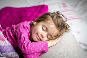 little girl sleeping in a pink bed