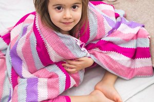 a little girl with a blanket in bed