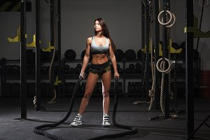 Young woman preparing to work out with battle ropes