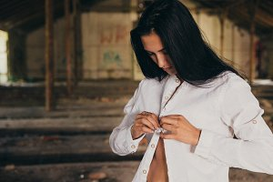 Young Woman Buttoning up Her Shirt