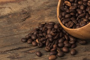 Raw coffee beans in wooden bowl