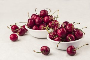 Fresh cherries on white bowls