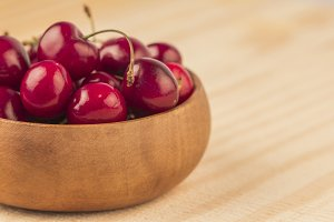 Fresh wet cherry on wooden bowl